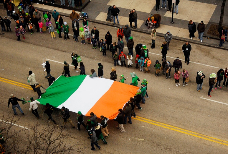 NICK SCHNELLE/JOURNAL STAR  A large Irish flag is carried down Main Street on Sunday during the St. Patrick's Day Parade in downtown Peoria.