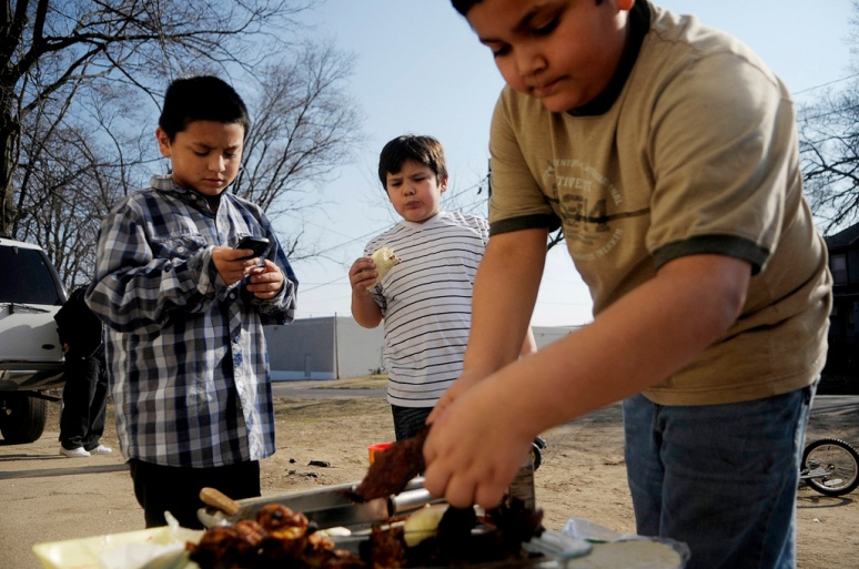 NICK SCHNELLE/JOURNAL STAR  From left, Benny Vargas, 8, Emanuel Nunez, 8, and Jose Ortiz, 10, cook tacos on the grill during warmer weather on Saturday afternoon outside a home on the 1000 block of Northeast Jefferson Avenue.
