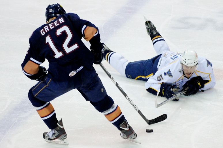 NICK SCHNELLE/JOURNAL STAR  Rivermen defenseman David Shields lays on the ice as he tries to take the puck away from Oklahoma City center Josh Green on Friday night at Carver Arena.