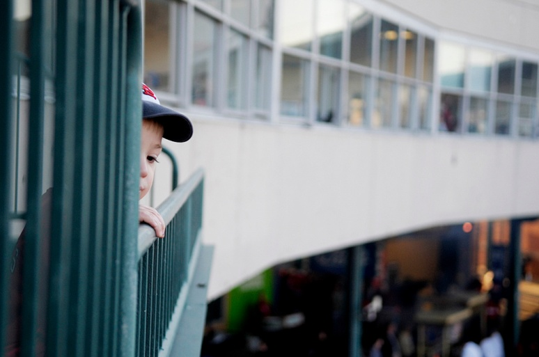 NICK SCHNELLE/JOURNAL STAR  Leo Fauser peeks over edge of the railing during the Peoria Chiefs home opener against the Wisconsin Timber Rattlers on Thursday afternoon at Peoria Chiefs Stadium.