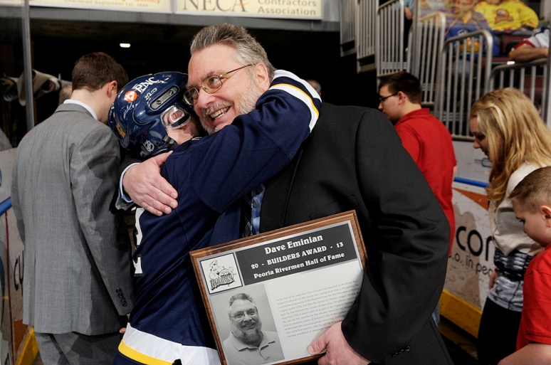 NICK SCHNELLE/JOURNAL STAR  From left, Adam Rosso gives a hug to Journal Star beat writer Dave Eminian after he was formally inducted into the Peoria Rivermen Hall of Fame on Saturday night at the Rivermen game at Carver Arena. Dave Eminian was in his 28th season covering the Peoria Rivermen for the Journal Star at the time of his induction.