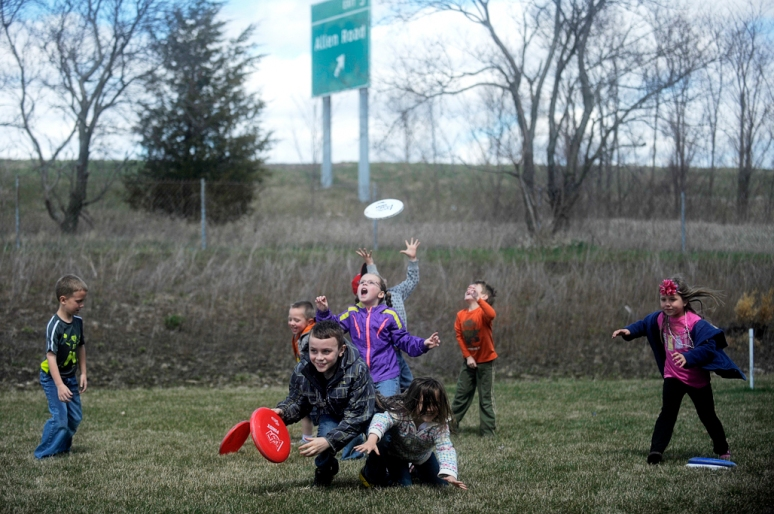 NICK SCHNELLE/JOURNAL STAR  Children scramble to catch Frisbees thrown from a robot during demonstrations by local high school robotics teams on Saturday as part of National Robotics Week outside the North Branch of the Peoria Public Library. Teams from three local high schools gave children introductions in robotics and provided hands on demonstrations of robots they've built.