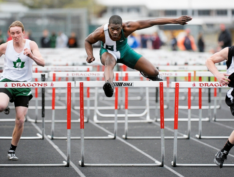 NICK SCHNELLE/JOURNAL STAR  Boys high school track athletes compete in the 110 high hurdles prelim at the Dragon Track and Field Invitational on Friday at Pekin Stadium.
