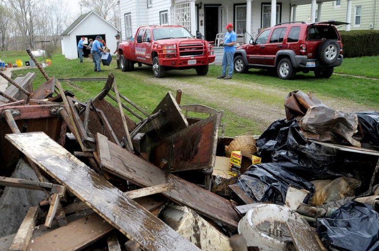 NICK SCHNELLE/JOURNAL STAR Items damaged from flooding are piled up at the curb of a home on Saturday as residents affected by recent flooding clean out their homes in London Mills.