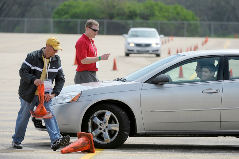 NICK SCHNELLE/JOURNAL STAR  From left, Rick Berlage pulls a cone from under the car of Matt Bender, 16, of East Peoria as event chairman Randy Jones, center, directs Bender on Sunday at the Tire Rack Street Survival teen driving program at Caterpillar's Mossville plant. With the assistance of in-car instructors, student drivers navigated an advanced driving course, which simulates real driving situations.